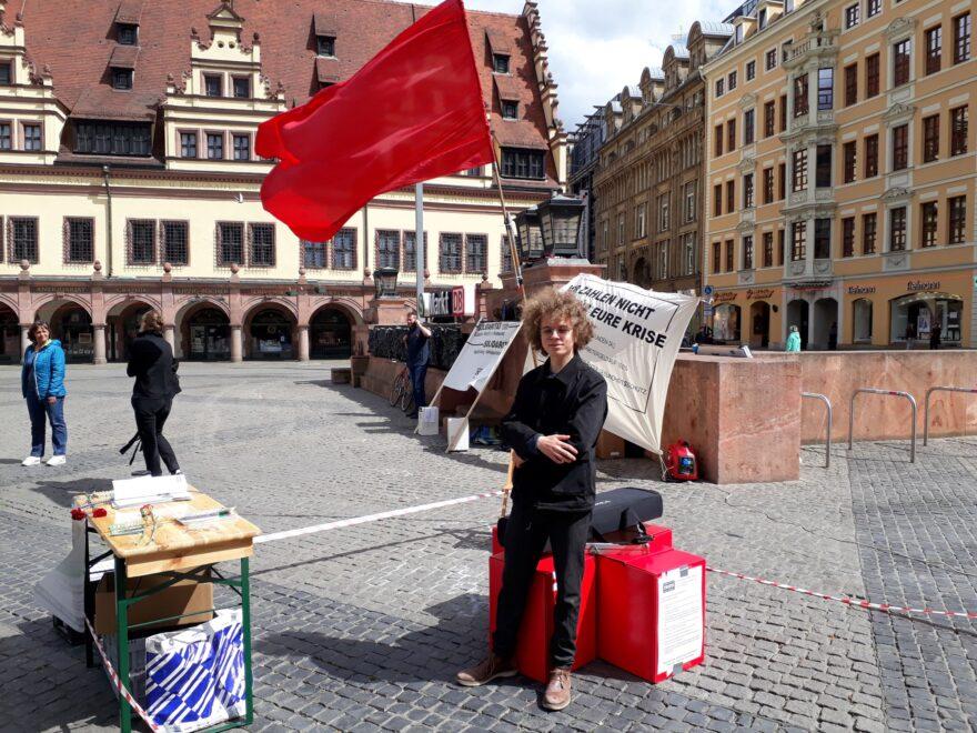 Mann steht vor einer roten Fahne am Ersten Mai in Leipzig.